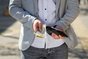 A man holding out money from his wallet.