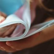 A person reading through a magazine.