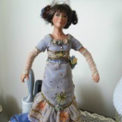Value of a Kathleen Hill Porcelain Doll - doll wearing a long blue dress with ruffled bottom over a dark blue underskirt