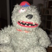 Identifying a Stuffed Bear - scraggly grey bear wearing a school type cap