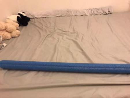 A pool noodle on top of a mattress.