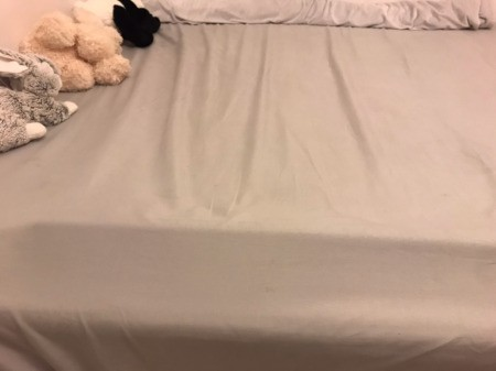 A pool noodle under the sheet of a made bed.