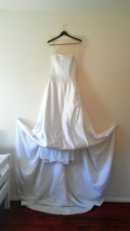 A wedding dress hanging on a wall.