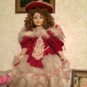 Identifying a Porcelain Doll - doll with hair in ringlets, wearing a red dress with lots of white and white with red trim ruffles