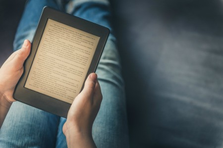 A person reading a Kindle in their lap.