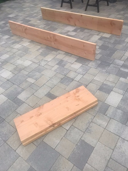 DIY Wooden Raised Garden Bed - two end pieces stacked nearby