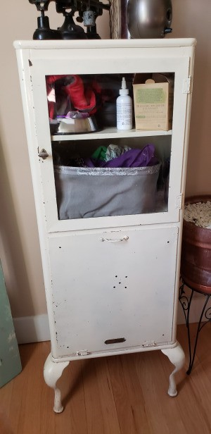 Value of an Aseptible Furniture Company Vintage Medical Cabinet - white metal cabinet with glass door and pull out bin