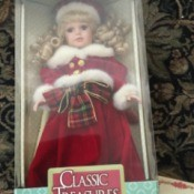 Value of a Classic Treasures Porcelain Doll  - doll wearing a red coat trimmed with white fur in the box