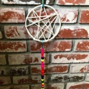 Dreamcatcher with Wooden Beads - dream catcher hanging against a brick wall