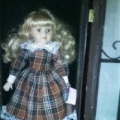 Value of a Ashley Bell Porcelain Doll - doll in black, brown, and white plaid dress