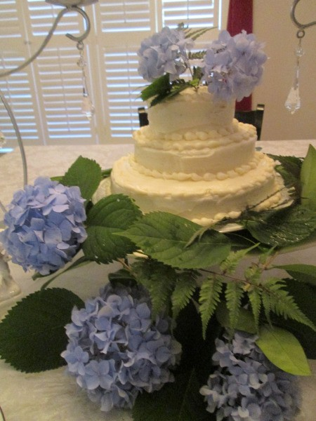A wedding cake decorated with hydrangea blooms.