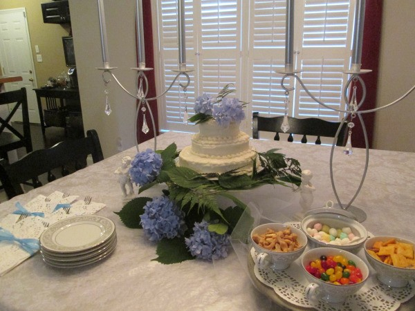 A decorated table with a wedding cake, china and some small dishes of snacks and candy.