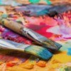 Two messy paint brushes on a palette.