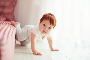 A toddler crawling out of a low bed.