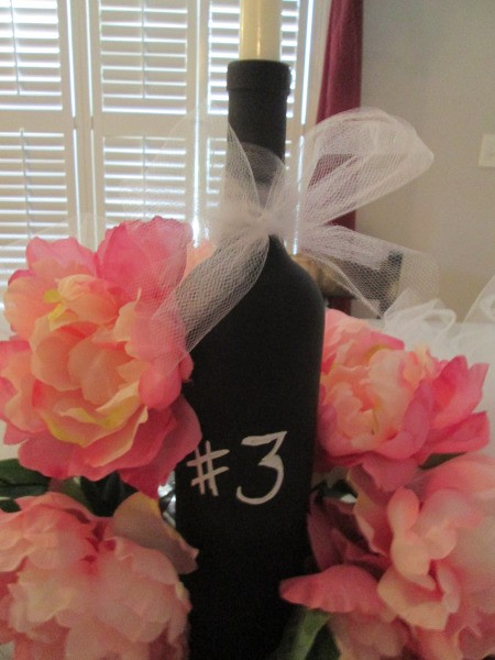 A spray painted wine bottle for marking table numbers.