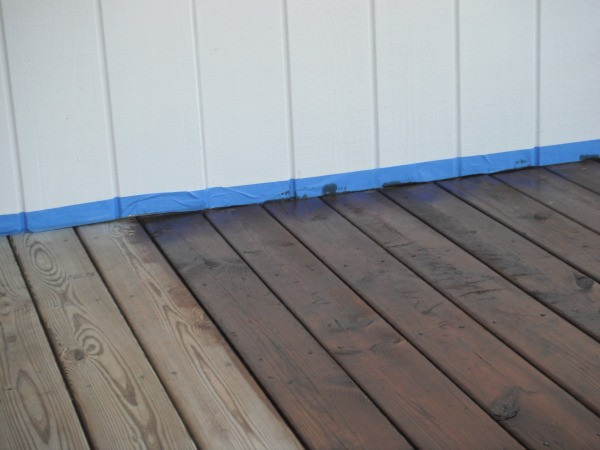 A blue line of painter's tape to protect the wall when staining a deck.