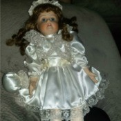 Identifying a Porcelain Doll - doll wearing a lace trimmed white satin dress with matching drawstring bag
