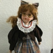 Identifying a Porcelain Doll - doll wearing a plaid dress with a dark jacket and matching hair bow, plus eyeglasses