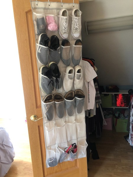 An over the door shoe organizer with shoes, socks and other accessories stored inside.