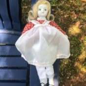 Identifying a Porcelain Doll - doll wearing a red print dress with a white pinafore over it