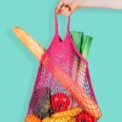 A grocery bag with fresh fruit and bread.