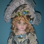 Identifying a Porcelain Doll - doll wearing a fancy blue dress trimmed with white lace