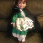 Identify and Value of a J. Misa Doll - doll wearing a green dress with a white eyelet apron and a dark cape