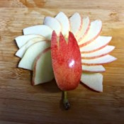How to Make Apple Bunnies and Flowers  - arrange slices as petals, top with the notched wedge, the apple stem serves as the flower stem