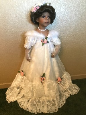 A porcelain doll with a white bridal outfit.