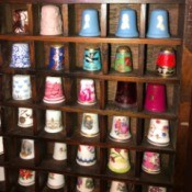 Finding the Value of Collectible Thimbles - wood rack filled with thimbles