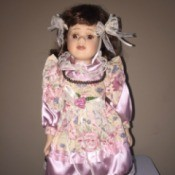 Identifying a Porcelain Doll - doll wearing a lavender dress with floral bodice, part of the sleeves, and an apron like layer