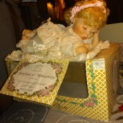 Value of a Crowne Porcelain Doll - baby doll lying on top of her box