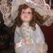 Value of an Elizabeth Gray Collection Doll - doll in white satin long dress with layers of lace and pink rosettes