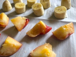 Fruit slices on parchment paper to be frozen individually.