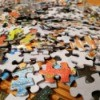 A pile of colorful cardboard puzzle pieces.