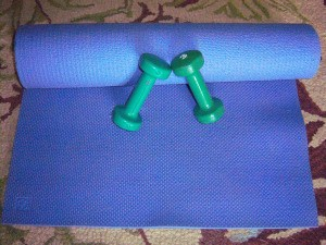 An exercise mat and a pair of dumbbells for exercising.