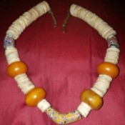 A beaded necklace with large orange beads.