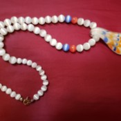 A beaded necklace with a colorful pendant.
