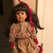 Value of a Connoisseur Collection Doll - doll wearing a red dress with lace trimmed floral bodice, sleeves, and overskirt