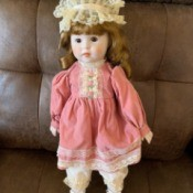 Identifying a Porcelain Doll - doll in pink dress with a lace cap