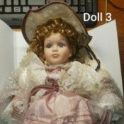 Identifying Porcelain Dolls  - curly haired doll wearing a pink dress with white lace