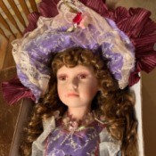 Value of a Cathay Collection Doll - fancy doll wearing a purple lace trimmed dress and matching hat