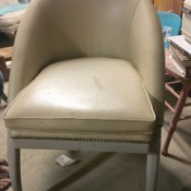 Identifying a Vintage Chair Style - half oval back, vinyl covered armless chair with brass studs across the front