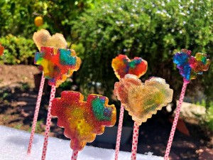 Making Rainbow Lollipops - lollies on sticks stuck into a piece of white foam packaging