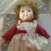 Identifying a Porcelain Doll - cute doll wearing a red dress with a floral pinafore look to it