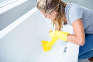 woman wearing gloves cleaning a tub