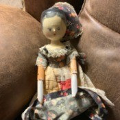 Identifying a Vintage Carved Wooden Doll - doll wearing a patchwork dress and a bonnet that is pulled back in this photo