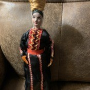 Maker of Beautiful Vintage Israeli Doll - doll wearing a long black dress with vertical decorations and carrying a basket on her head