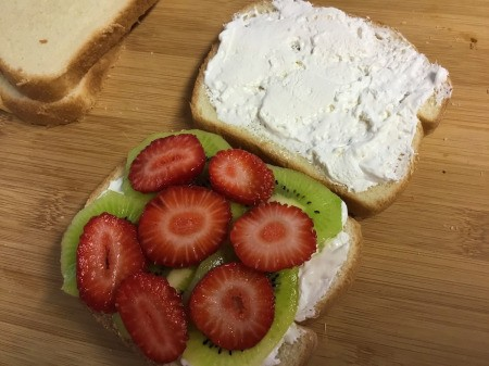 whipped cream on bread with sliced kiwi & strawberries