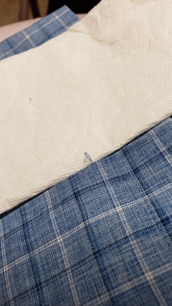Repairing Clothing Snags - snag isolated against a paper towel
